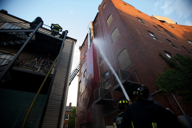 5.27.2010 — BOSTON — Firefighters hose down a kitchen vent that caught fire at Olive's restaurant, 10 City Square in Charlestown, on May 27, 2010. The two-alarm fire caused heavy smoke and was likely caused by a grease backup in the air vent, Boston Fire spokesman Steve McDonnell said.
