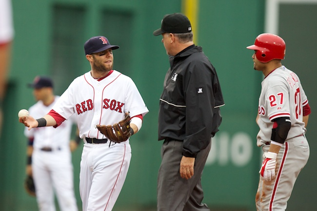 6.13.2010 — BOSTON — Red Sox second baseman Dustin Pedroia argues a safe call for Phillies third baseman Placido Polanco, right, on a close play at second with umpire Paul Emmel in the eighth inning on June 13, 2010.