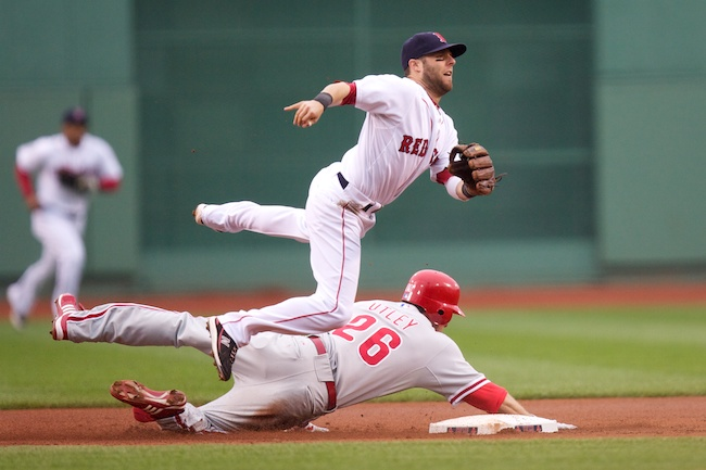 6.13.2010 —BOSTON — Red Sox second baseman Dustin Pedroia gets taken off his feet by Phillies second baseman Chase Utley after turning a double play to end a bases-loaded jam in the first inning on June 13, 2010.