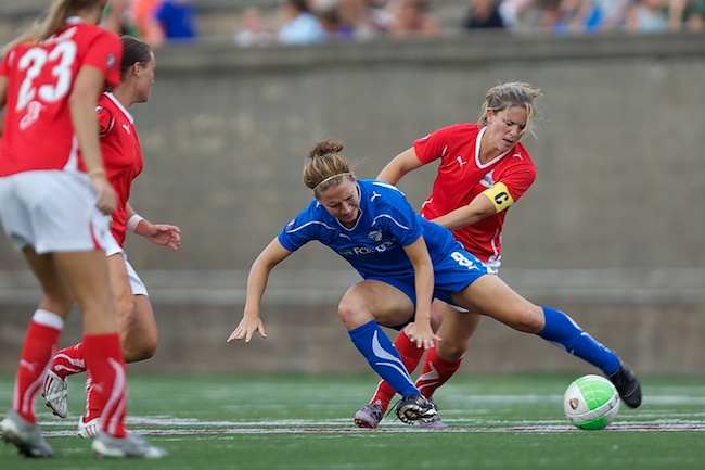 7.18.2010 — BOSTON — Boston Breakers striker Lauren Cheney gets a push from Washington's Cat Whitehill in Boston's 2-1 win on July 18, 2010.